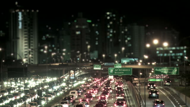 night city traffic with defocused buildings in background - 聖保羅 個影片檔及 b 捲影像
