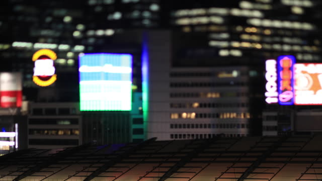a night cityscape near the station at the business town in tokyo handheld high angle - segnale per macchine e pedoni video stock e b–roll
