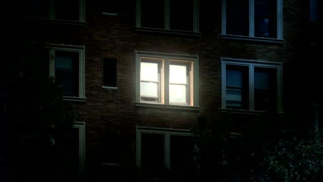 night establishing shot of office windows lights turning on and off - appartamento video stock e b–roll