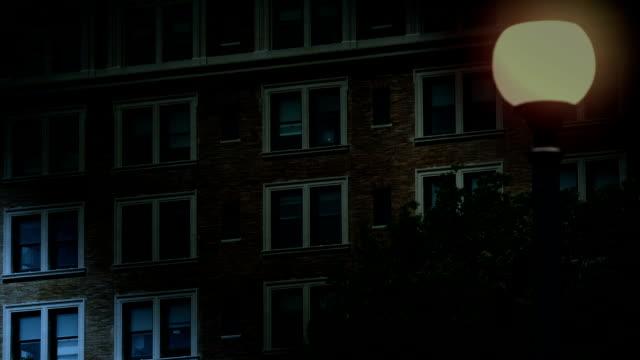 night establishing shot of office windows lights turning on - apartments stock videos & royalty-free footage