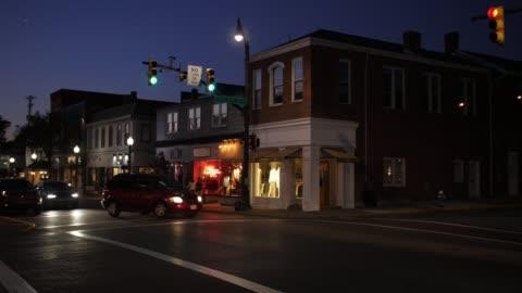 vídeos y material grabado en eventos de stock de establecimiento de tiro de esquina de calle principal americano típico pequeño pueblo de la noche - calle principal calle
