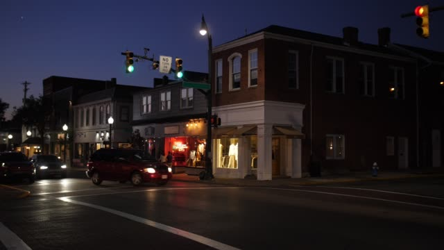 night establishing shot of typical american small town main street corner - пешеход стоковые видео и кадры b-roll