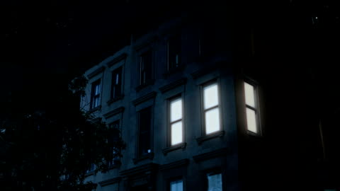 Night Establishing Shot of Typical Brooklyn Brownstone Upper Floors A nighttime exterior establishing shot of the upper floors of a typical Brooklyn brownstone residential home as a room lights up then turns off. apartment stock videos & royalty-free footage