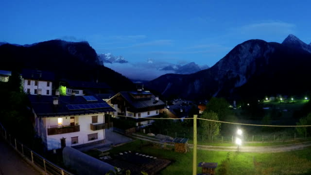 Night falling on beautiful comfy cottages in mountain area, European village video