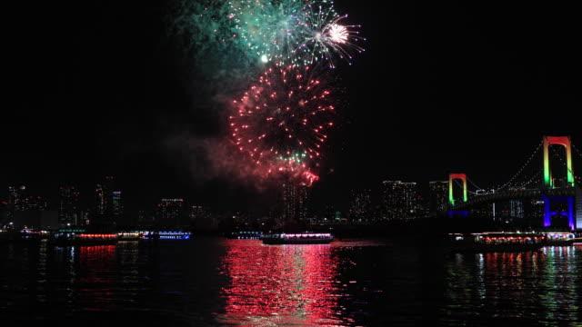 Ein Nachtfeuerwerk in der Nähe der Regenbogenbrücke in der Stadt in Tokio weit geschossen – Video