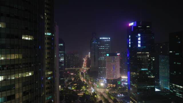 night illuminated flight over hangzhou city downtown traffic street aerial panorama 4k china - vídeo