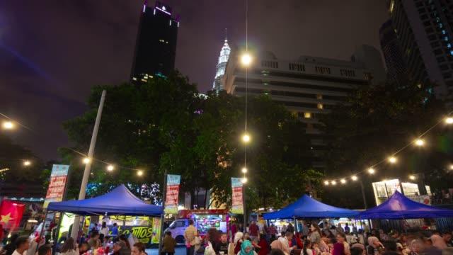 vídeos de stock, filmes e b-roll de noite iluminado kuala lumpur centro da cidade comida de rua lotado mercado panorama 4k timelapse malásia - junk food