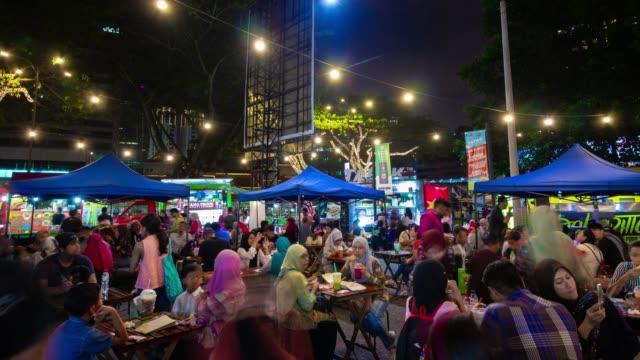 night illuminated kuala lumpur city center street food crowded market panorama 4k timelapse malaysia - malaysia video stock e b–roll