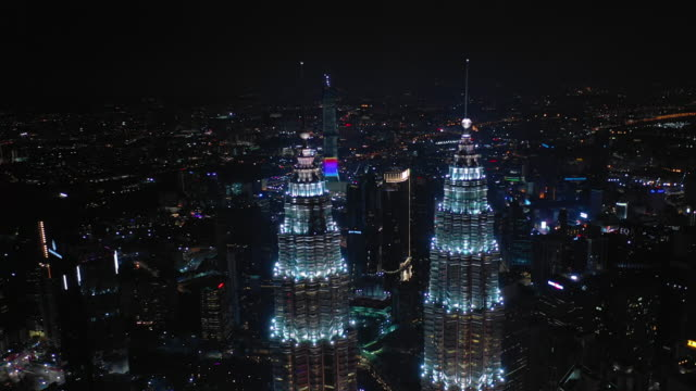 natt upplyst kuala lumpur centrum berömda torn toppar antenn panorama 4k malaysia - petronas twin towers bildbanksvideor och videomaterial från bakom kulisserna