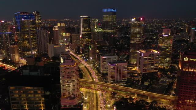 night illumination flight over jakarta city downtown busy traffic street road aerial panorama 4k indonesia video