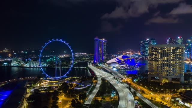 vídeos de stock, filmes e b-roll de noite iluminação singapura arquitectura da cidade tráfego estradas flyer panorama aéreo 4k timelapse - marina