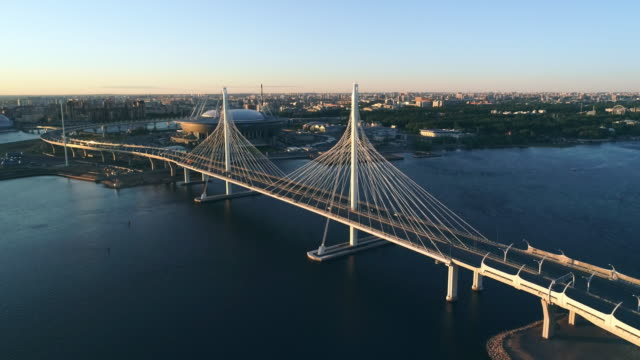 Night landscape of a flat city Top view of a well-lit modern cable-stayed bridge at sunset treedeo saint petersburg stock videos & royalty-free footage