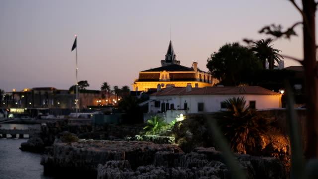 vídeos de stock e filmes b-roll de noite paisagem de cascais lisboa rivera portugal com marina na praia dos pescadores, albatros edifício - vídeos de barragem portugal