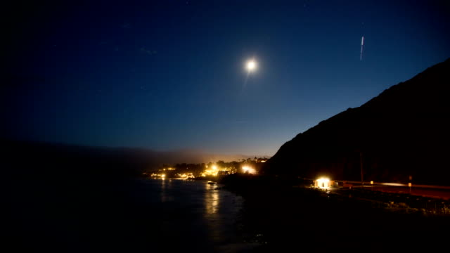 vídeos de stock e filmes b-roll de night moon moves across the sky just after sunset. cars travel along the coastal highway. moon reflection on the ocean. timelapse. - estrada 001