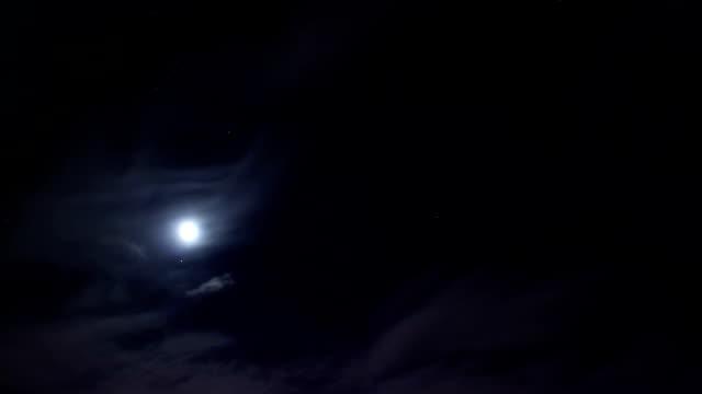 Night moon sky timelapse, clouds move pass dark, stars shine
