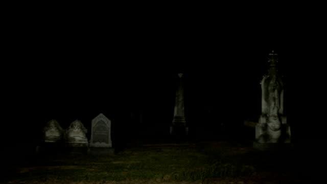 Night pan across cemetery graveyard video