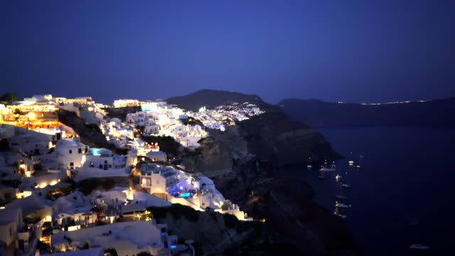 night pan from the town of fira to oia on the island of santorini - fire filmów i materiałów b-roll
