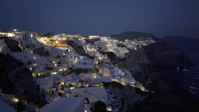 night pan to the left of the main town of fira on santorini - fire filmów i materiałów b-roll