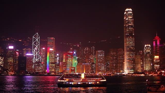 ビクトリア ・ ハーバーで前景にフェリーで香港のスカイラインの夜景。 ビデオ