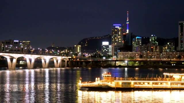 vídeos de stock e filmes b-roll de night scenry of seoul city with ferry passing by and n south tower in background - seul