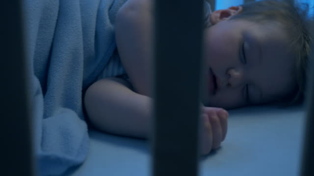night shot-söt bebis fredligt sova i sin spjälsäng - baby sleeping bildbanksvideor och videomaterial från bakom kulisserna