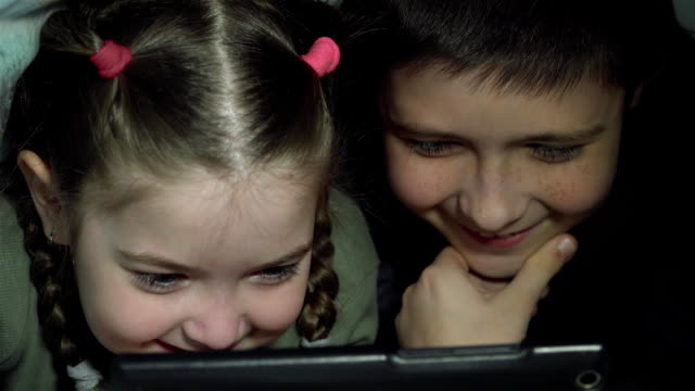 Natt skott av barn pojke och flicka ansikten surfar tablet pc och spela tv-spel under filt video