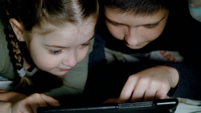 Natt skott av tonåring pojke och flicka med tablet pc under filt. Glada barn leker med mobiltelefon eller smartphone på sängen under karantän video