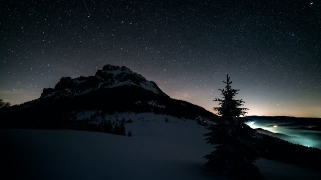 night sky with stars moving over mountain peak in winter astronomy time lapse - наклон вверх стоковые видео и кадры b-roll