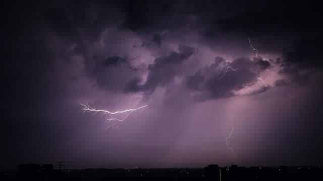 vidéos et rushes de ciel de traîne de nuit au-dessus de ville. ensemble de beaux coups de foudre. nuages d'orage. timelapse. slow motion - ciel orageux