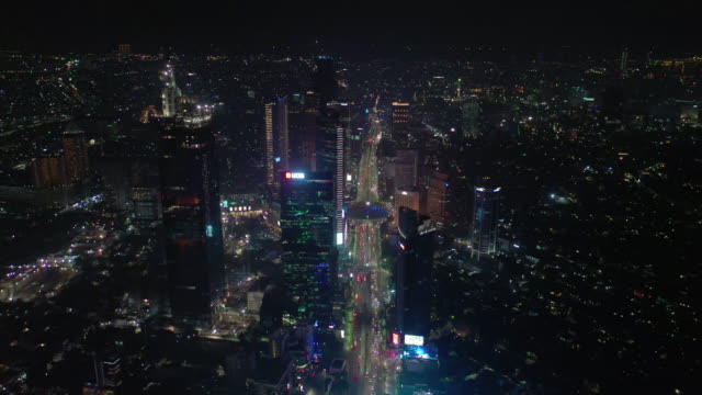 night time illuminated jakarta central cityscape traffic street circle fountain aerial panorama 4k indonesia video