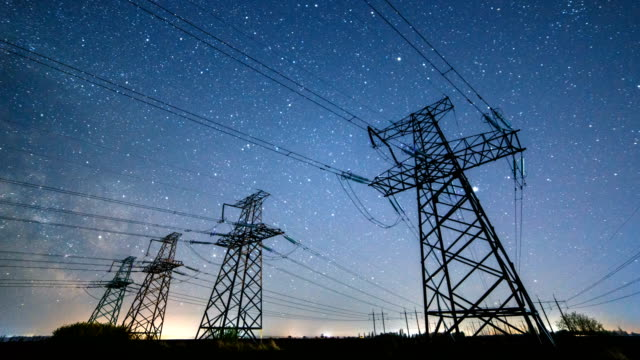 Night time lapse of high-voltage power lines on the background of the starry sky.