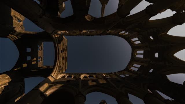 vídeos y material grabado en eventos de stock de lapso nocturno de la salida de la luna sobre la abadía - material de construcción