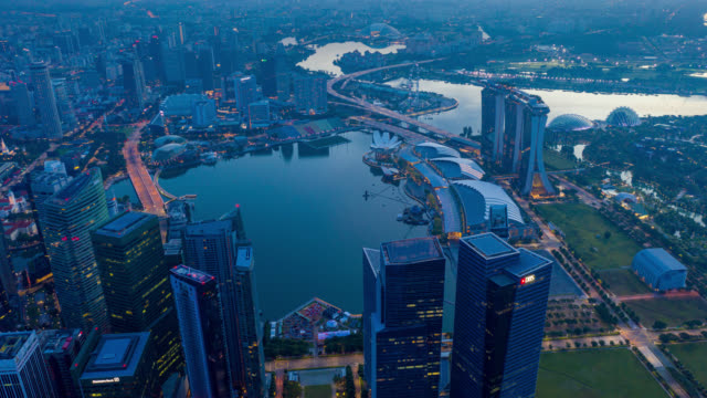 Night to day Hyperlapse or Dronelapse scene of Singapore business district downtown at sunrise