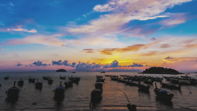 Night to day Time Lapse, Sunrise at harbour long tail boats on ocean surface near the Lipe island.