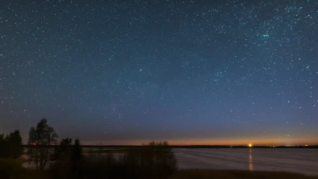 night to sunrise timelapse over lake - cielo stellato video stock e b–roll