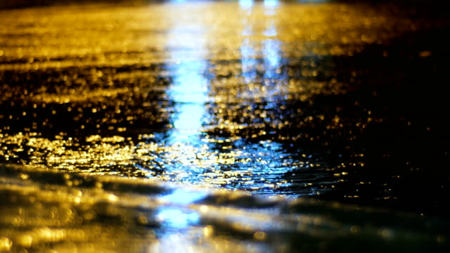 Night traffic light reflect on water surface in rainy day video