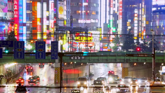Night traffic road and crowded with banner sign on tall building in the city while raining