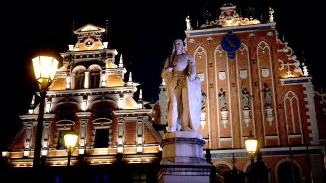 nattvisning av ett monument till roland på rådhustorget mot bakgrund house of blackheads riga lettland - ancient white background bildbanksvideor och videomaterial från bakom kulisserna