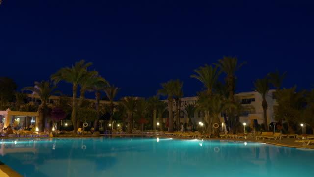 Night view of illuminated swimming pool near hotel building, timalapse