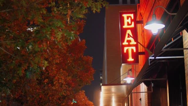 ネオンの夜景が市看板を食べる - 建物の正面点の映像素材/bロール