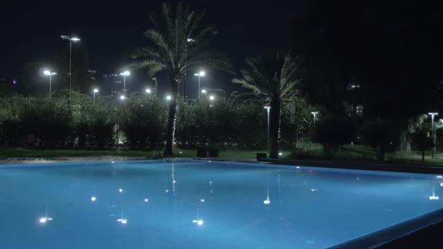 vidéos et rushes de vue de nuit de piscine sur resort - lieu sportif