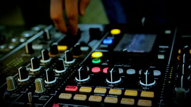 Nightclub DJ adjusting controls, twisting toggle on professional soundboard video