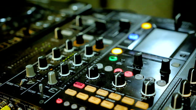 Nightclub DJ playing mix on soundboard, console with flashing lights and buttons video