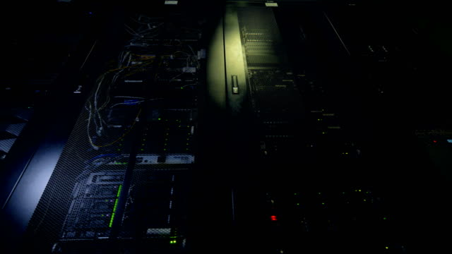 A nighttime continuous work of data storage equipment. Several working data center cabinets with tuned on switches and drives inside. backup stock videos & royalty-free footage