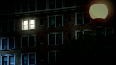 """Nighttime Establishing Shot of Late Night Worker in Office Building A typical New York style apartment or office building establishing shot at night with the light from only one window on. Simulated """"day-for-night"""" composite. apartment stock videos & royalty-free footage"""