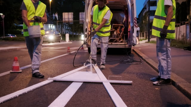 Nighttime Pavement Marking Crew Spray Painting Turn Arrow Construction crew member concentrating on spray painting new turn arrow in Central European capital city street. civil engineering stock videos & royalty-free footage