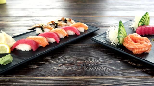 Nigiri and sashimi, wooden table. video