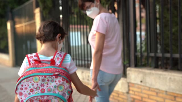 vídeos de stock e filmes b-roll de nine years old girl with bag walking with her mother hand in hand. - ffp2