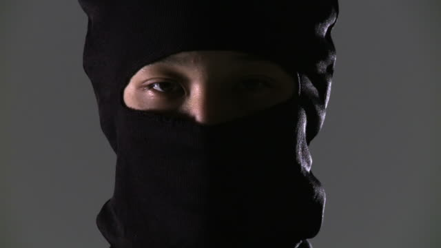 Ninja Close Up Camera pans and tilts to reveal a close up of a masked ninja assassin.  Two clips. ninja stock videos & royalty-free footage