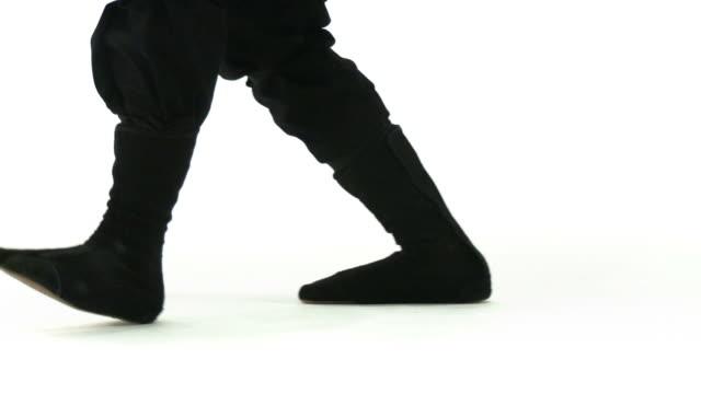 Ninja Feet Pan Panning camera follows ninja feet as they walk on a white background. ninja stock videos & royalty-free footage